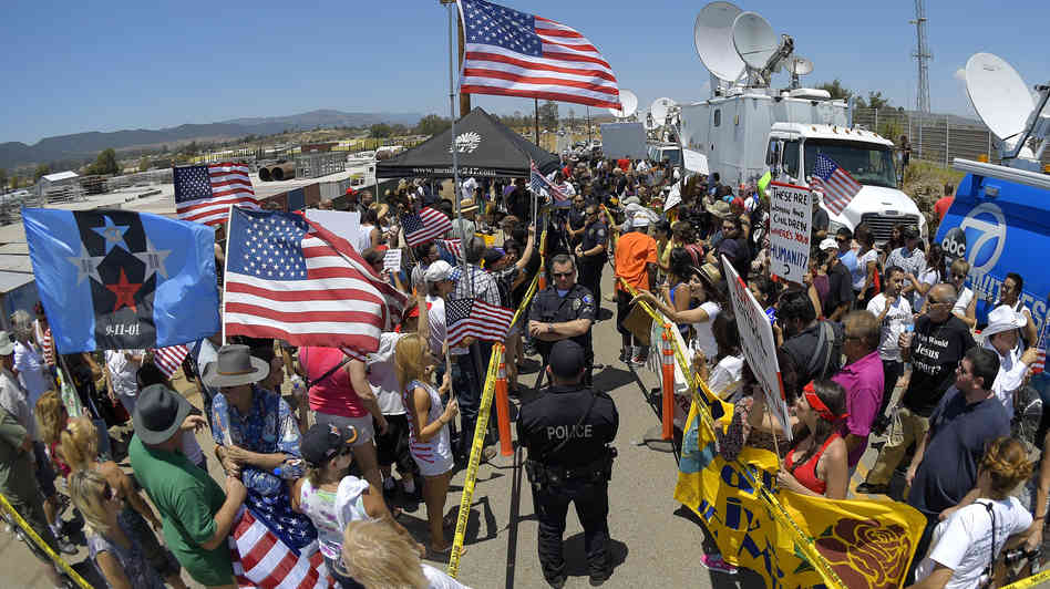 Police officers separate demonstrators on opposing sides of the immigration debate outside a U.S. Border Patrol station in Murrieta, Calif., on July 4.