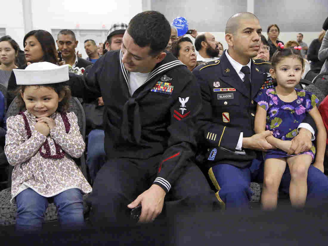 Navy Petty Officer Jimmy Dial, left, sits with his daughter Kimberly beside U.S. Army soldier Henri Blandon and his daughter as the men's wives and the girls' mothers become U.S. citizens at a naturalization ceremony last month in Ontario, Calif.