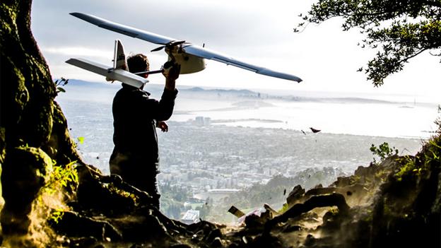 A man launching a 3D Robotics Aero-M drone